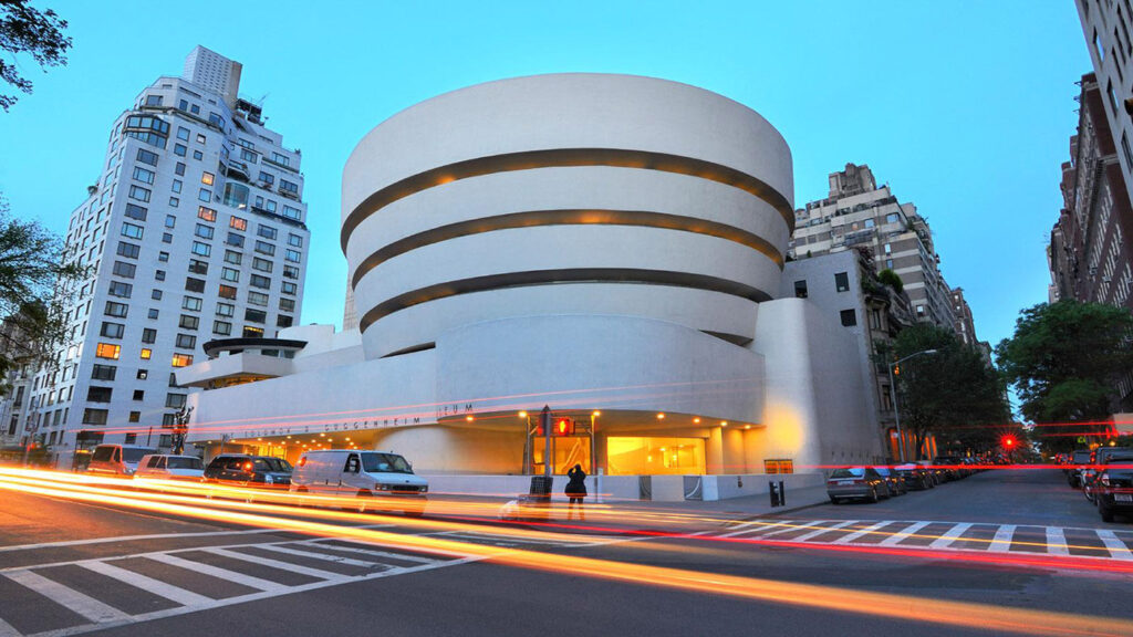 The Entrance to the Solomon R. Guggenheim Museum in New York City with Black Cars speeding By.